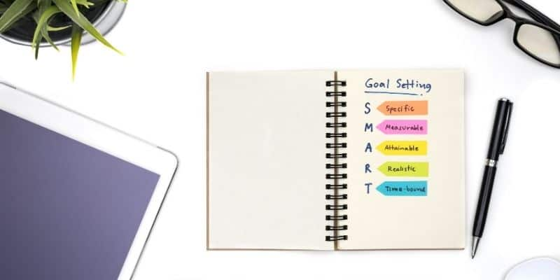 notebook on a white desk with _goal setting_ and S.M.A.R.T. acronym and black ink pen